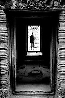 A tourist admires The Bayon temple in the walled city of Angkor Thom, Siem Reap, Cambodia