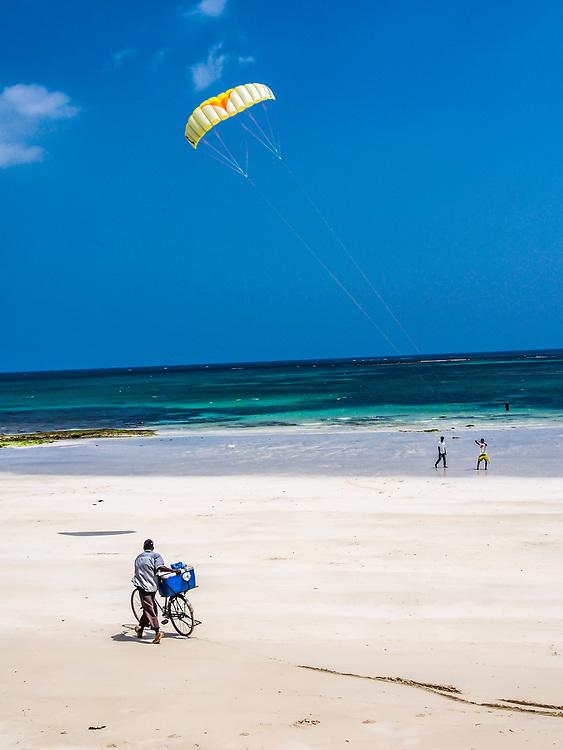 A seller watches kite flying at Tiwi beach, Kenya.