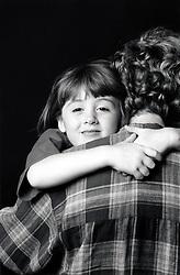 Parent cuddling daughter, UK 1990s