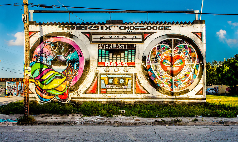 In 2010 an Argentine street artist named Sonni painted an abandoned Wynwood building to resemble a boombox.<br /> <br /> But someone painted an advertisement over his two-story-tall art work.<br /> <br /> So, in 2012, Miami street artist, Trek6, and San Francisco-based artist Chor Boogie, reimagined The Boombox Building with a different design, which you see here.<br /> <br /> A few years later The Boombox Building -- by now a local landmark -- was repainted again, in the version shown in the next three images in this online gallery.