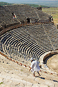 Tourist walk down the benches inside the Roman Theatre at Hierapolis, the roman site at the top of Pamukkale. Tthe he hard, white mineral deposits of Pamukkale, which from a distance resemble snow, are caused by the high mineral content of the natural spring water which runs down the cliff and congregates in warm pools on the terraces. This is such a popular tourist attraction that strict rules had to be established in order to preserve its beauty, which include the fact that visitors may no longer walk on the terraces. Those who want to enjoy the thermal waters, however, can take a dip in the nearby pool, littered with fragments of marble pillars.