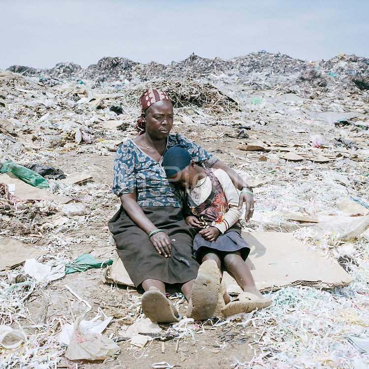 """Florence Khalumbia (46) With daughter Alice (7 ) lives just 50 metres from the """"California"""" dumpsite in a one-bedroom hut with her five children. None of the children go to school – she feels that it's better that they stay home and help their family to earn a living. Alice, the youngest, is seven years old, and she spends her days sorting through rubbish with her 14-year-old brother Allan Karani. They've never had any formal education and neither can read or write. Florence does want her children to improve their situation, but so that they can look after her. The family manages to earn just over a dollar a day from sorting rubbish at the dumpsite but that is not enough to buy food for the family."""