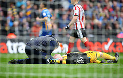 Shrewsbury Town's Dean Henderson receives treatment after colliding with Lincoln City's Matt Rhead during the Checkatrade Trophy final at Wembley Stadium, London.