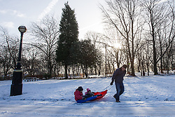 © Licensed to London News Pictures . 26/01/2013 . Salford , UK . A man pulls two children on sleds through the snow . People enjoy fresh overnight snow this morning (26th January 2013) in Buile Hill Park , Salford . Photo credit : Joel Goodman/LNP