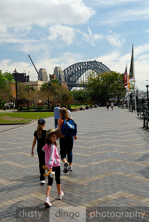 Mother and two daughters (6 years old and 10 years old) walking toward Sydney Harbour Bridge. Circular Quay, Sydney, Australia