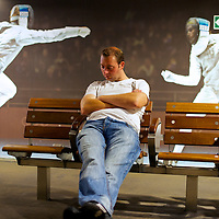 A man slumbers on the platform while waiting for the Javelin train from Stratford International Station at 3am during the 2012 London Summer Olympics.