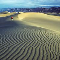 A hiker walks across Mesquite Sand Dunes in California's Death Valley National Park.