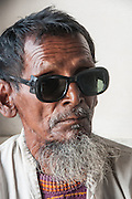 Bangladesh, Jamuna River, (called the Brahmaputra River in India) near the town of Gaibanda. This is the boat based Friendship non-profit organization (NGO), who provide health care and vocational traing  for locals. This is a portrait of a man wearing dark sunglasses who recently had a cataract eye operation. He is waiting for a check-up.