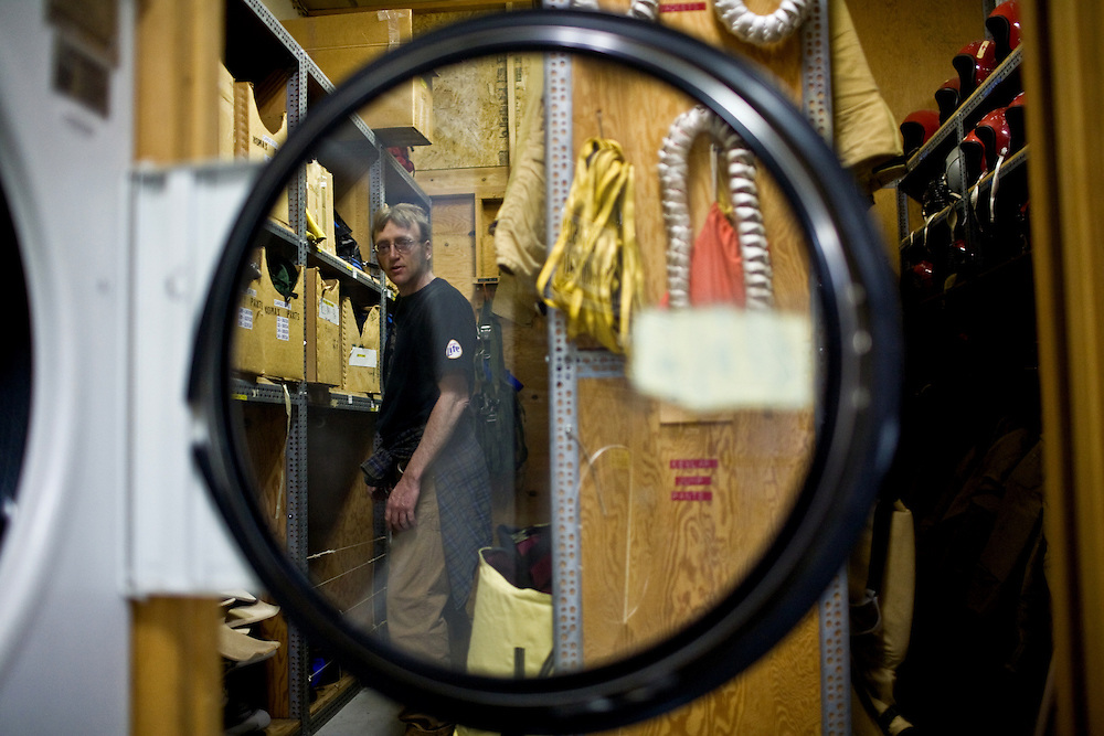 Laundry is another less-than-glamorous component of the smokejumper's profession, but is required to keep the operation running. Brett Bittenbender stands in the equipment room.