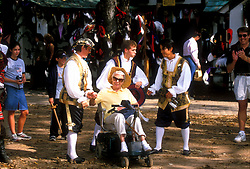 Stock photo of three men in costume posing with an older woman at the Texas Renaissance Festival in Plantersville Texas