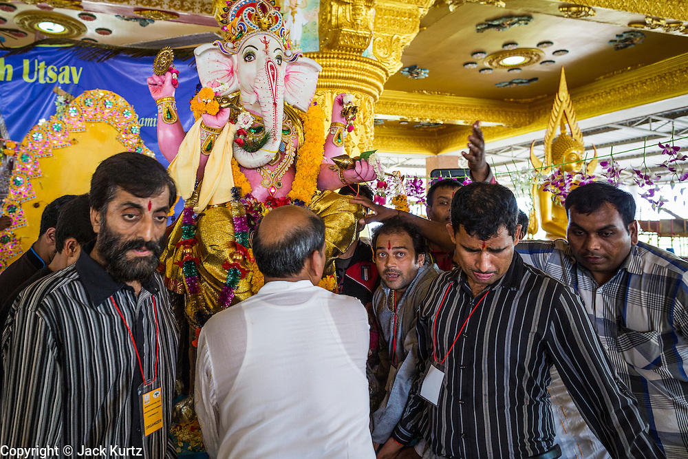 """15 SEPTEMBER 2013 - BANGKOK, THAILAND: Hindu men carry a statue of Ganesha to a waiting truck on the last day of Ganesha Chaturthi celebrations at Shiva Temple in Bangkok. The deity was taken to the Chao Phraya River and submerged. Ganesha Chaturthi is the Hindu festival celebrated on the day of the re-birth of Lord Ganesha, the son of Shiva and Parvati. The festival, also known as Ganeshotsav (""""Festival of Ganesha"""") is observed in the Hindu calendar month of Bhaadrapada. The festival lasts for 10 days, ending on Anant Chaturdashi. Ganesha is a widely worshipped Hindu deity and is revered by many Thai Buddhists. Ganesha is widely revered as the remover of obstacles, the patron of arts and sciences and the deva of intellect and wisdom. The last day of the festival is marked by the immersion of the deity, which symbolizes the cycle of creation and dissolution in nature. In Bangkok, the deity (statue) was submerged in the Chao Phraya River.     PHOTO BY JACK KURTZ"""