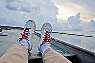 Sneakers on boat out in the marsh between Isle de Jean Charles and Pointe-Aux-Chien in Terribone Parish Louisiana. The Island is under constant threat of flooding due to coastal erosion.