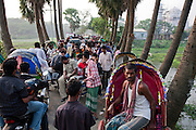 Tourists negotiate their way to the Taj Mahal Bangladesh, a replica of India's famed Taj Mahal erected by Ahsanullah Moni, a millionaire film director and business man from Bangladesh. He says he built it because most  Bangladeshi people cannot afford the trip to Agra, India to see the real thing. The entry fee for his replica is 50 Taka, about  0.75 USD. There is a 25-room hotel facing the Bangla Taj and he says his plans include a film studio and center nearby. The construction of the main Taj will be completed in about a month but the tourist attraction is now open to the public. Moni claims about 20,000 people visit daily. There is only a single lane two kilometer road winding through the surrounding rice fields connecting the main road to his attraction, near the town of Sonargaon, about 30 kilometers from Dhaka.