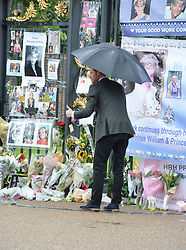 Prince Harry after he took a bouquet of flowers from a wellwisher to add to the tributes to Diana, Princess of Wales attached to the Golden Gates of Kensington Palace, London, ahead of the 20th anniversary of his mother's death.