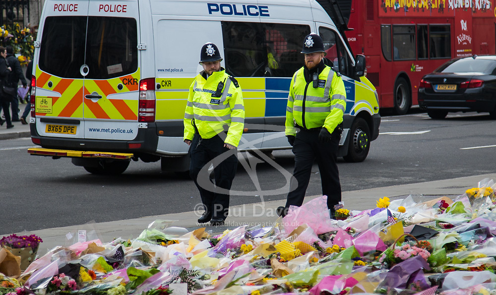 Westminster, London, March 27th 2017. Two police officers walk past the thousands of floral tributes to the victims of March 22nd's terror attack in Westminster which claimed the lives of four people including police officer and the attacker and injured many others, some critically. Credit: ©Paul Davey<br /> <br /> ©Paul Davey<br /> FOR LICENCING CONTACT: Paul Davey +44 (0) 7966 016 296 paul@pauldaveycreative.co.uk