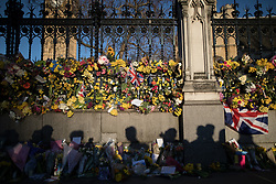 © Licensed to London News Pictures . 25/03/2017 . London , UK . The shadows of onlookers in front of flowers left by the Carriage Gates outside Old Palace Yard at the Houses of Parliament in Westminster . PC Keith Palmer and several pedestrians were murdered by Khalid Masood . Photo credit : Joel Goodman/LNP