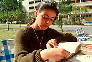 MEXICO, EDUCATION, MEXICO CITY College student reading on campus of U.I.C.