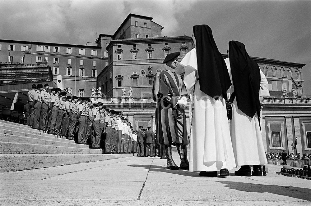 Nuns talking to member of the Swiss Guards while waiting for the Pope to attend his weekly audience at St Peter's Square. TheVatican, Rome, Italy.