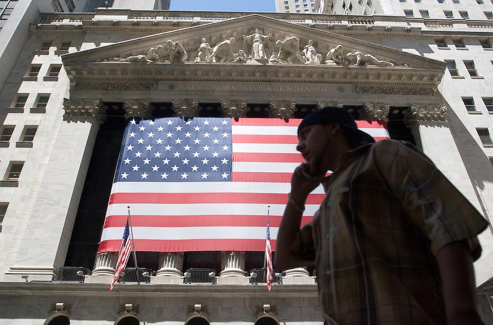 Un joven latino hablando por el móvil pasa por delante del famoso edifio de la bolsa en Wall Street.