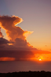 Offshore thunderstorm at sunset with heavy rain pouring from enormous, anvil cumulonimbus clouds, Kona Coast, Big Island, Hawaii, Pacific Ocean.