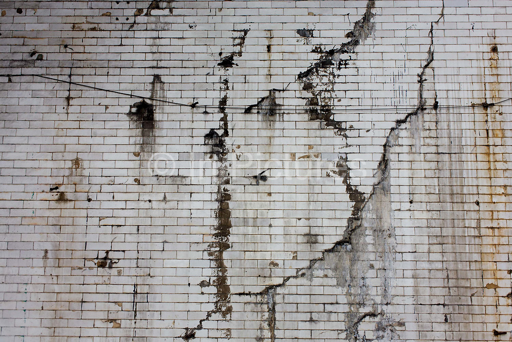 Cracked and split tiling on the wall under a railway bridge in south London. Located in the borough of Southwark, we see the tiles in a state of disrepair, neglected and left to deteriorate. Diagonal cracks and brown stained, we look up at the aging surface - its dirty pallor originallly white.