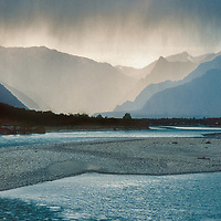 A rain squall hovers over the Yarlung Tsangpo River, north of the Himalaya in Tibet, China.
