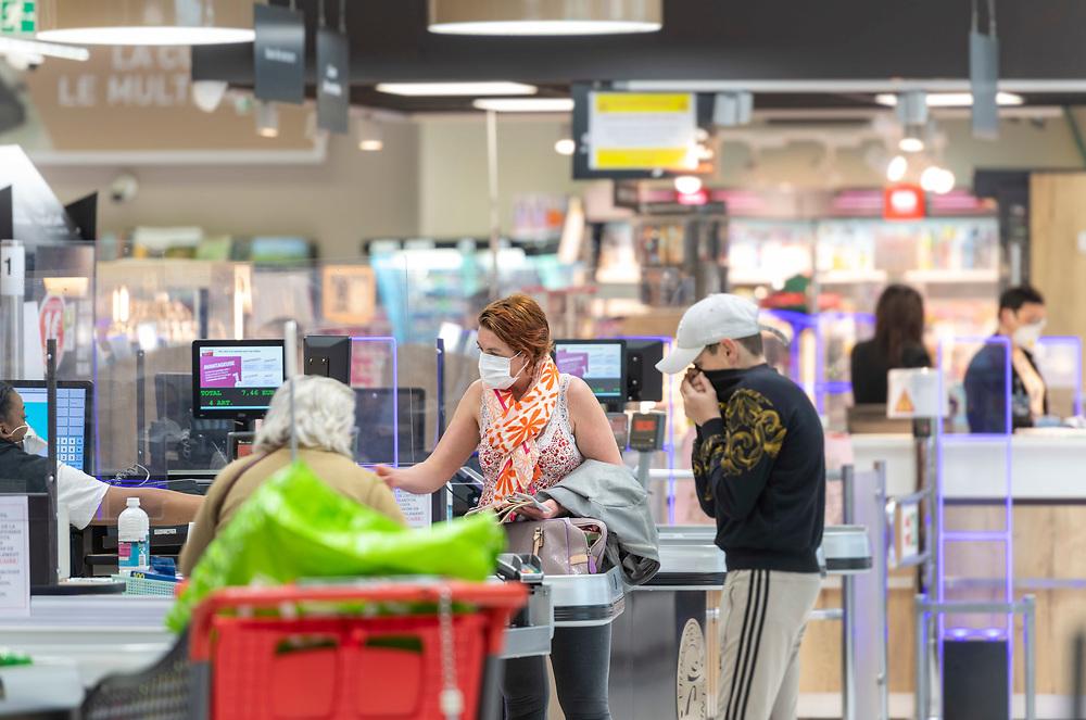 L'Intermarché de La Loupe, le 18 mars 2020, Une cliente , portant un masque anti-virus , règle ses courses à la caisse du supermarché.