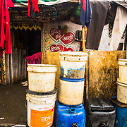 CAPTION: Containers filled with water are frequently seen stacked up outside houses, a reflection of inadequate water supply. LOCATION: Chikitsak Nagar, Indore, Madhya Pradesh, India. INDIVIDUAL(S) PHOTOGRAPHED: N/A.