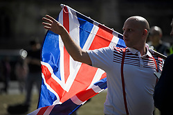 © Licensed to London News Pictures. 31/08/2019. London, UK. A group of Brexit supporters waving the Union Flag form a counter demonstration in Parliament Square as pro Eu Protestors gather near 10 Downing Street in Westminster, London as part of a nationwide 'Stop The Coup' day of action against Boris Johnson's plans to suspend parliament. More than 80 demonstrations are planned across the UK in response to government plans to prorogue parliament. Photo credit: Ben Cawthra/LNP