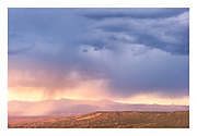 Rain virgas over the Rio Grande Valley, as viewed from the High Road. Cerro Pedernal on horizon at right.