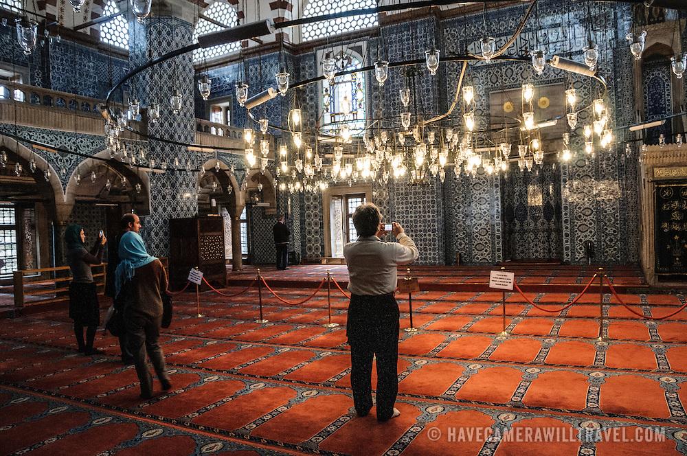 Tourists take photos inside Istanbul's Rustem Pasha Mosque near the Spice (Egyption) Market.