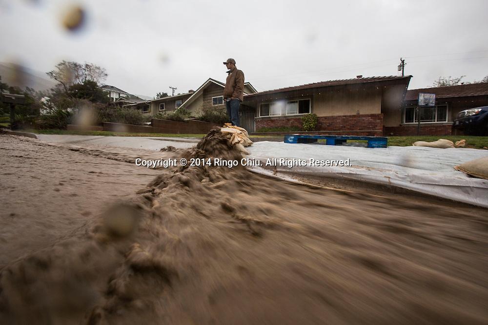 12月2日,美國加利福尼亞州洛杉磯,大量黃泥水從山上流到民居前。當天南加州迎來秋天第一場暴雨,將為今年面臨嚴重乾旱問題的加州帶來2至5寸雨水。 同時,當局亦發出警告,洪水、土石流可能會襲擊部分地區。 (新華社發 趙漢榮攝) <br />  A man keeps watch of the mud and debris flowing along the street from the burnt areas in Los Angeles, California, Tuesday, December 2, 2014. California is bracing for the arrival of a new, more powerful Pacific storm following a weekend of scattered rain, showers and snow. The National Weather Service says a low-pressure system off the coast will draw a plume of subtropical moisture northward into the state beginning on Tuesday.  (Xinhua/Zhao Hanrong)(Photo by Ringo Chiu/PHOTOFORMULA.com)