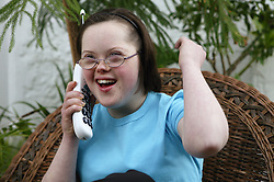 Teenage Downs Syndrome girl laughing on the telephone,