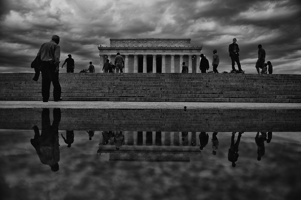 Visitors of the Lincoln Memorial are reflected in a puddle after a passing storm.