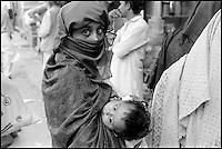 Pakistan, Punjab, Femme voilée avec sion bébé dans le bazar de Rawalpindi. // Pakistan. Punjab. Veiled woman with baby at Rawalpindi bazar.
