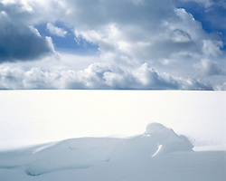 Abstracted view of snowfield with humanlike shape in foreground and breaking storm clouds in background