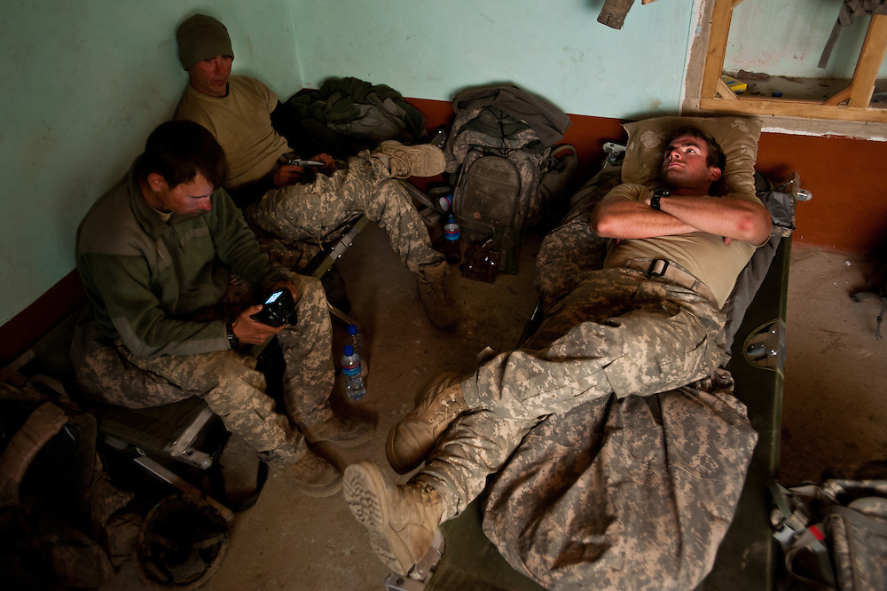 First Lieutenant Mark Hogan, right, rests in an Afghan compound with members of his platoon after a day of patrolling.
