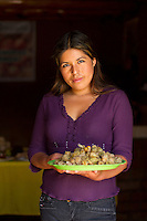 Young woman holding plate of ground cherries, Peru.