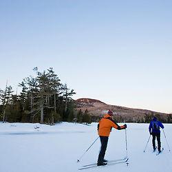 Cross-country skiers on a frozen pond near Little Lyford Pond Camps near Greenville, Maine, Winter. Indian Mountain is in the distance.