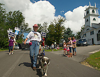 Mona Smith marches with her Australian Shephards Mabel and Peanut in Sanbornton's Old Home Day parade on Saturday.  (Karen Bobotas/for the Laconia Daily Sun)