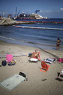 Tourist on the beach near the Costa Concordia wreck after the parbuckling operation