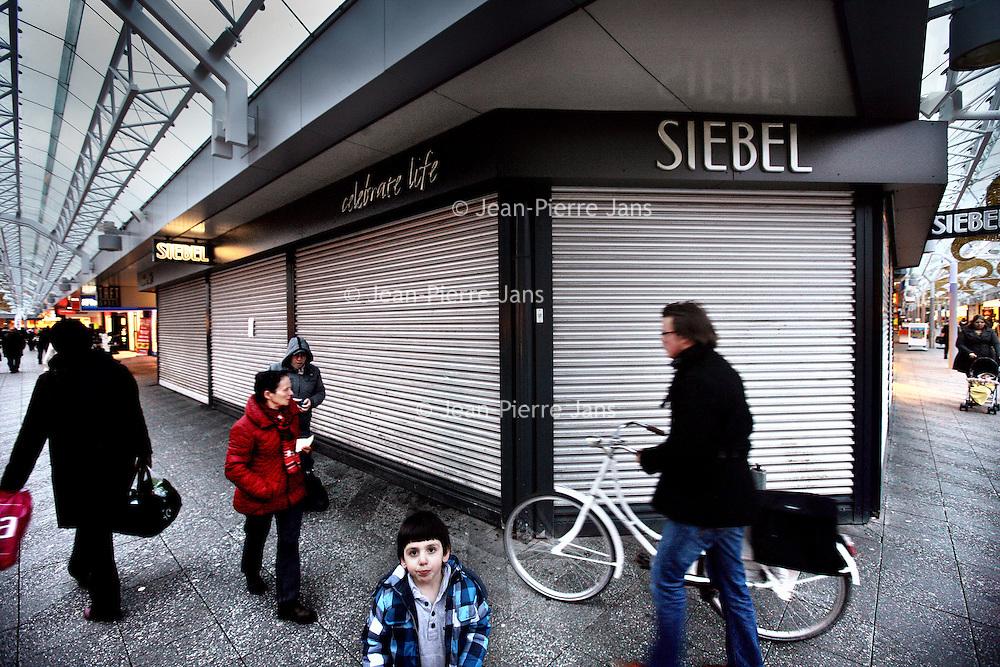 Nederland, Amsterdam , 17 januari 2014.<br /> Juweliersketen Siebel verkeert in grote problemen. Vandaag zijn, zo bevestigt de klantenservice van het bedrijf, alle 36 winkels en de webshop dicht.<br /> De directie meldt dat er binnenkort meer duidelijkheid zal komen over de toekomst van Siebel Juweliers en zijn medewerkers. Er werken 170 mensen bij de juweliersketen. Eerder vandaag ontkende een woordvoerder van Siebel dat het bedrijf failliet is.<br /> Op de foto:  Gesloten Siebel filiaal op het Buikslotermeerplein in Amsterdam Noord.<br /> Foto:Jean-Pierre Jans