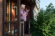 As the number of UK deaths from Coronavirus reaches 37,837, a further 377 in the last 24hrs) a grandmother stands outside her house to clap for the NHS (National Health Service) key worker heroes for the last time during the UK Coronavirus pandemic lockdown, on 28th May 2020 in London, England.
