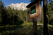 The rural lake 'Lêch della Lunch' in the Badia Dolomites, south Tyrol. Italy. The natural lake is located above the town of Pedraces/Badia Abtei and is seen early morning as the sun shines off the signpost, in forest with white rock rising in the background.