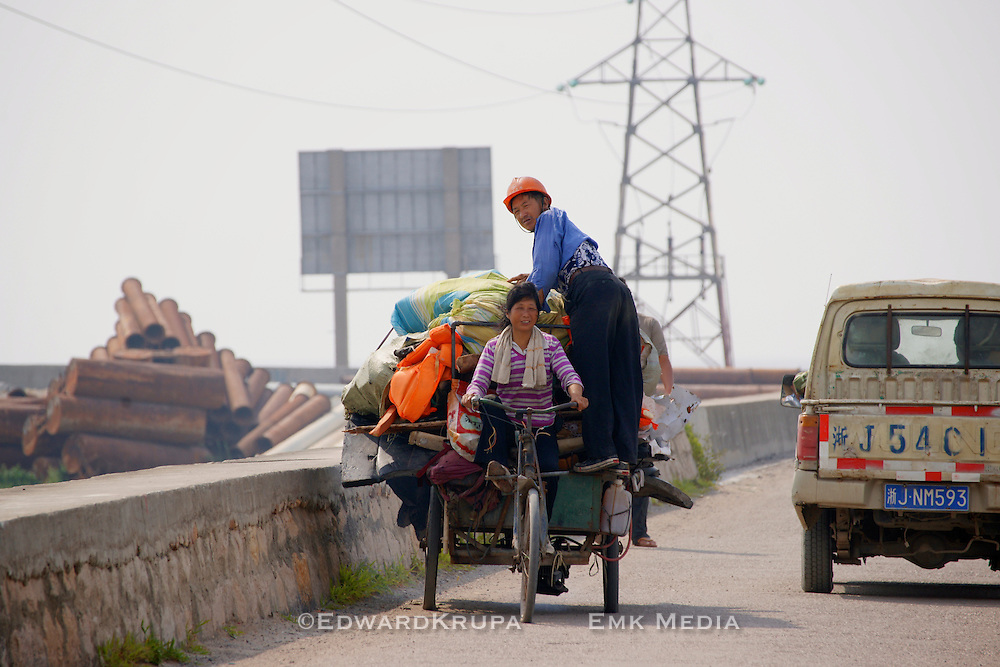 Family moving some stuff on a makeshift 3 wheeled motorbike near the South China Sea.