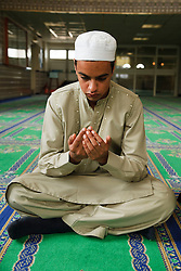 Muslim boy asking for a blessing in a Mosque.
