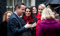 © London News Pictures. 10/11/2012. London, UK. British Prime Minister David Cameron talking to members of the Military Wives Choir who performed on Downing Street before members of the Royal Marines from Commando 999 (Royal Marines who serve with the UK emergency services) took part in a  speed march for charity around London in record time to raise funds for wounded service personnel. The event takes place on Remembrance weekend.  Photo credit: Ben Cawthra/LNP