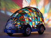 Stained-glass mini isn't a pane to drive at all: British designer creates driverless vehicle which features a bed and was inspired by the Durham Cathedral<br /> <br /> A British designer has created a bedroom with a view - and when you wake up, you may well be at your chosen destination.<br /> <br /> Dominic Wilcox designed his vision for the future of transport - a stained glass covered driverless car which contains a bed - for an exhibition at the London Design Festival last week. <br /> <br /> Mr Wilcox said by 2059, he believed it would be 'statistically proven' that computer controlled driverless cars were safer than those driven by people. At which point, he said 'we will simply require a living space on wheels'.<br /> Mr Wilcox said his idea for the stained glass shell of the vehicle came out of his 'interest in taking what I admire from objects of the past and merging it with technology of the future, to create a new future'.<br /> <br /> And it followed a visit to the Durham Cathedral where he was 'struck by the wonderful stained glass'.<br /> <br /> Mr Wilcox said: 'I wanted to bring the visual experience I had in the cathedral into a new, contemporary, three dimensional form.'<br /> <br /> He said the hand cut glass on the car used the same technique used to make the famous Tiffany lamps.<br /> The glass shell is supported by a computer designed and manufactured frame which brings together 'bespoke craftsmanship with the technical precision of computer aided design'.<br /> <br /> Mr Wilcox said the car also took design inspiration from the original mini launched in 1959, using classic mini tyres, and the boot handle, which is now used as a handle to open the glass shell to get inside.<br /> ©Dominic Wilcox/Exclusivepix