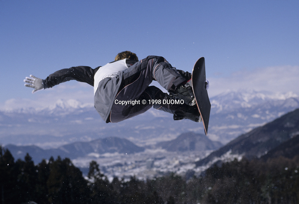Male snowboarder flying over the vert.