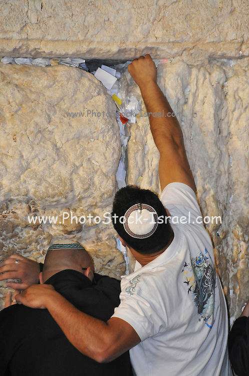 Israel, Jerusalem, Wailing Wall, Jews during Selichot prayers. Selichot (Selihot?) are Jewish penitential poems and prayers, especially those said in the period leading up to the High Holidays, Man places note in the wailing wall